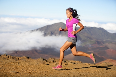 an athlete: Runner woman athlete running sprinting fast. Female sport fitness model training a sprint in amazing nature landscape outdoors at speed wearing sporty runners clothing outfit. Mixed race Asian woman