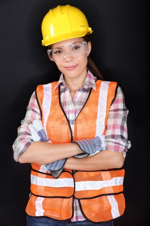 safety goggles: Construction worker with safety vest, glasses and hardhat portrait on black background. Portrait of young asian chinese  caucasian model