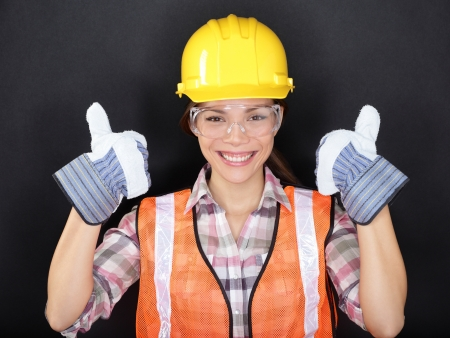 security vest: Construction worker happy woman doing thumbs up with protection wear. Young woman wearing safety glasses, vest and yellow hard hat for security and protection on black background. Asian female model. Stock Photo
