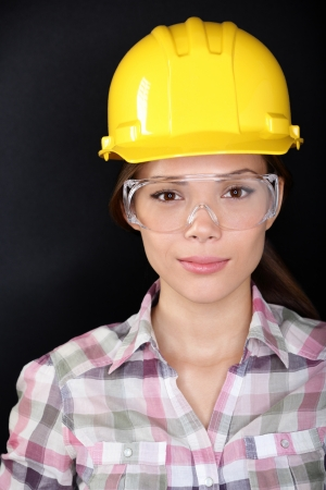 head wear: Construction worker woman with safety glasses and hardhat. Portrait of female contractor on black background. Stock Photo