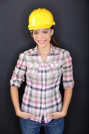 Construction worker woman portrait. Young woman wearing safety glasses and yellow hard hat for security and protection. Multiracial Asian model smiling happy on black background. photo