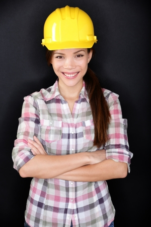Female construction worker, home owner in renovations or engineer posing on black background. Young woman wearing yellow protection hard hat smiling happy. Multiracial Asian model. photo