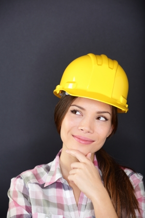 hard look: Young female architect, engineer, surveyor or construction worker wearing hardhat thinking as she standing with hand to chin looking thoughtfully to the side, studio portrait on a dark background
