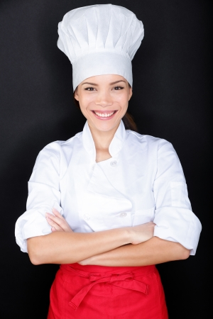 chinese hat: Asian female chef in chef whites uniform and hat. Woman chef, cook or baker portrait on black background. Young multiracial Chinese Asian  Caucasian female model standing proud and cross-armed.