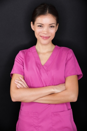 scrub: Female nurse portrait happy confident in pink scrubs on black background. Young woman medical professional nurse or doctor standing cross-armed looking at camera smiling. Multiracial Asian model.