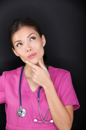 Doctor  medical female nurse thinking looking up. Woman medical professional looking thinking at empty black background copy space. Multi-ethnic Asian Caucasian doctor or nurse in pink scrubs. photo