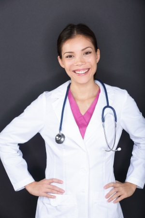 health service: Female medical doctor woman portrait. Happy smiling young medical professional in lab coat with stethoscope looking at camera on black background. Multi-ethnic Asian Caucasian female model. Stock Photo