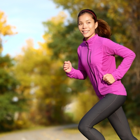 Young Asian woman running female jogger happy. Female runner jogging in park in autumn park forest in fall colors. Beautiful young sport model. Multi-ethnic Asian Chinese  Caucasian girl in her 20s. photo