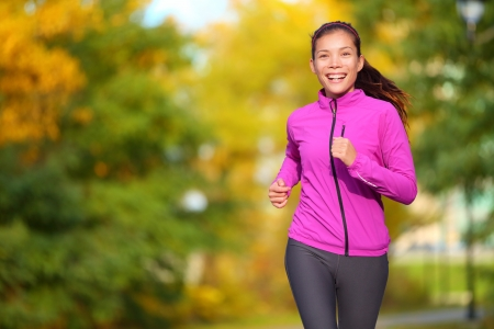 Vrouwelijke jogger. Fit jonge Aziatische vrouw joggen in park glimlachende gelukkige lopen en genieten van een gezonde outdoor lifestyle. Fitness loper meisje in de herfst bos met bladeren vallen. Gemengd ras Aziatische Kaukasische.