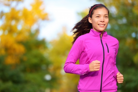 Running woman jogging in autumn forest in fall. Beautiful female runner wearing autumn running jacket. Healthy lifestyle photo with beautiful mixed race ethnic Chinese Asian and Caucasian fitness girl photo
