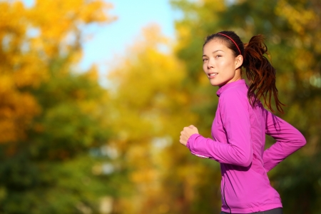 Aspirations - Aspirational woman runner running looking and thinking about future goals. Female athlete jogging in autumn forest in fall color foliage. Beautiful multiracial Asian Caucasian jogger. Stock Photo