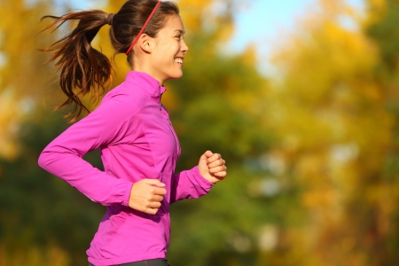 Woman running in autumn fall forest. Female runner training outdoor in profile. Healthy lifestyle image of young Asian woman jogging outside. Fit ethnic Asian Caucasian fitness model. photo