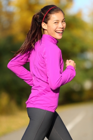 Asian woman running - female runner in autumn forest fall foliage colors. Jogginh fit sports fitness girl smiling laughing happy looking at camera. Beautiful energetic mixed race Asian Caucasian model photo