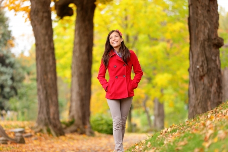 Fall girl walking on Autumn forest path smiling happy and joyful with fresh candid smile. Young beautiful mixed race Asian Chinese  Caucasian female model girl in 20s enjoying fall foliage outdoor. photo