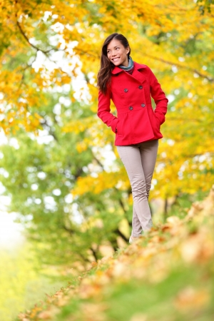 Beautiful young woman fall autumn nature scene with fall foliage. Slender stylish young woman walking in colourful yellow autumn woodland with a lovely relaxed smile, low angle looking up the hillside photo