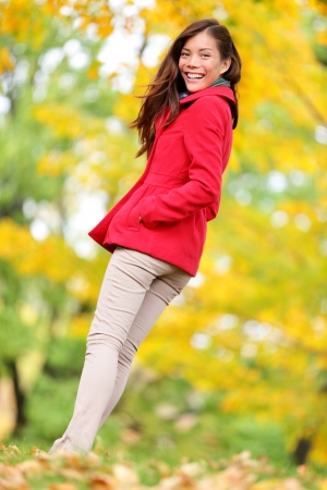 Autumn people - fall woman walking in colorful forest foliage. Happy female full length autumn concept portrait of young Asian woman enjoying fall colors smiling happy outdoor. Multiracial Asian photo