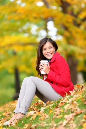 Happy woman drinking coffee in fall forest  city park outdoor. Girl sitting relaxing enjoying hot drink, coffee or tea in disposable cup outside in beautiful fall foliage. Asian Caucasian female, 20s photo