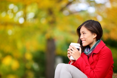 Autumn  fall woman drinking coffee looking at forest foliage copy space thinking. Happy smiling multi-ethnic Asian Chinese  Caucasian female model in red coat enjoying hot drink outdoor. photo