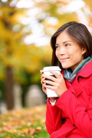 People drinking coffee - autumn woman in fall forest enjoying hot drink, coffee or tea, from disposable cup. Beautiful female outdoor in autumn colors, red, orange and yellow. Mixed race Asian girl. photo