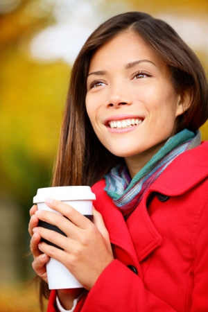 Autumn woman drinking coffee in fall city park or forest. Beautiful fall colors and happy smiling Asian girl drinking coffee or tea from disposable cup outdoor. Multiracial Asian girl in her 20s. photo