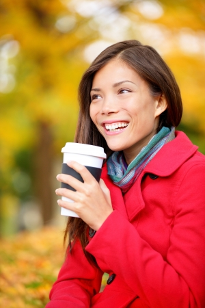 Coffee drinking woman in Autumn fall enjoying fall and hot drink from disposable cup. Smiling happy Asian female model in fall foliage. Mixed race Asian Chinese  Caucasian girl in her 20s. photo