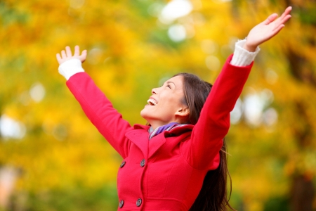 alabando a dios: Otoño  caída mujer feliz en libertad sin pose con los brazos levantados hacia el cielo con una sonrisa alegre, eufórico expresión de la felicidad. Hermosa chica en el bosque colorido follaje al aire libre. Foto de archivo