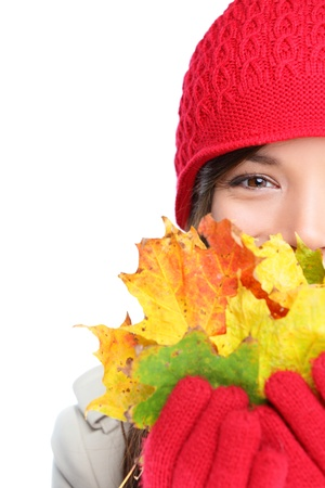Autumn woman happy with colorful fall leaves isolated on white background in studio. Cheerful girl hiding behind autumn leaves. Portrait close up of multiracial mixed race Asian Caucasian female model photo