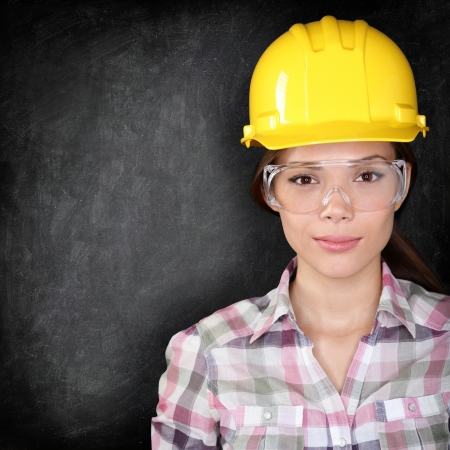 eye protection: Serious woman construction worker, home owner in renovations or engineer face on black background texture with chalkboard for copy space. Young woman wearing safety glasses and hard hat.