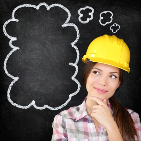 Thinking young female construction worker, architect, engineer, surveyor wearing hardhat on blackboard thinking with hand to chin looking to the thinking bubble on chalkboard texture. photo
