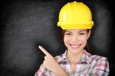 Female construction worker or engineer showing pointing at empty blackboard with copy space for your text on chalkboard. Young woman wearing yellow hard hat smiling happy. Multiracial Asian model. photo