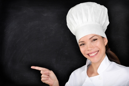 chefs whites: Chef pointing showing blank menu blackboard. Happy female chef, cook or baker showing empty chalkboard menu display. Woman wearing chef whites uniform and hat on black blackboard background.