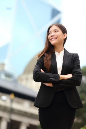 Businesswoman confident outside. Business woman standing proud and successful in suit among skyscrapers buildings. Young multiracial Chinese Asian  Caucasian female professional in central Hong Kong. photo