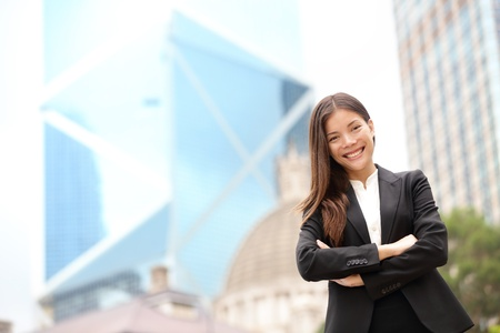 real leader: Young Asian business people business woman portrait outside. Businesswoman standing proud looking at camera in suit. Multiracial Chinese Asian  Caucasian female professional in central Hong Kong.