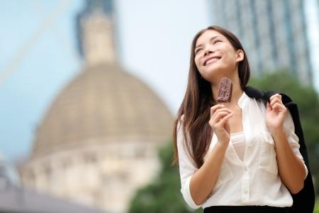 ice cream on a stick: Mujer de negocios que come el helado en Hong Kong. Joven empresaria disfrutando de helado en al bast�n fuera feliz y sonriente en el centro de Hong Kong. Carrera de modelo de Asia  cauc�sica china Mixta de descanso