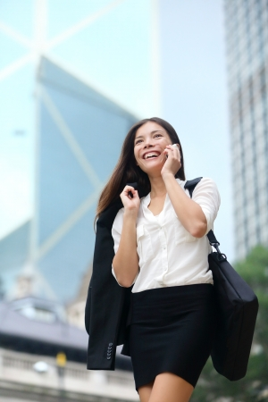 Business woman talking on phone outdoor, Hong Kong. Asian business people office worker talking on smartphone smiling happy. Young multiracial Chinese Asian / Caucasian female professional outside. photo