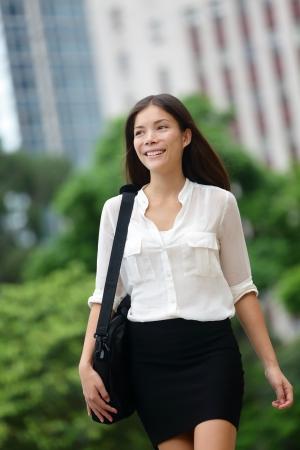 女性歩行ビジネスカジュアル Hong kong 屋外。アジアの実業家のオフィス ワーカー ブリーフケースを保持している.多民族国家中国アジアコーカサス