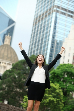 Business achievements success businesswoman in Hong Kong celebrating business goals with arms raised up as winner. Young mixed race Chinese Asian  Caucasian female professional in Hong Kong central. photo