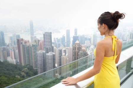 Hong Kong Victoria Peak Asian tourist woman enjoying view over Hong Kong Island and Victoria Harbour. Young happy mixed race Asian Caucasian girl traveling in Asia wearing yellow summer dress. photo