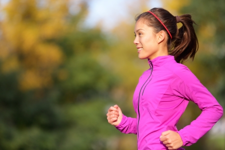 warm jacket: Asian woman running in autumn forest in fall. Female runner training outdoor in warm running outfit. Beautiful multi-ethnic Chinese Asian  Caucasian female jogging. Stock Photo