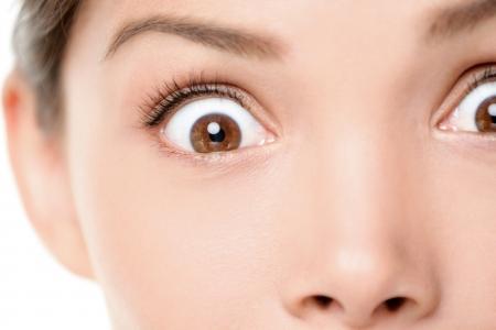 Verbaasd  geschokt gezichtsuitdrukking van de vrouw. Verrassing en schok close-up van vrouwelijke ogen kijken naar de camera. Gemengd ras Aziatische Kaukasische vrouwelijke model met bruine ogen.