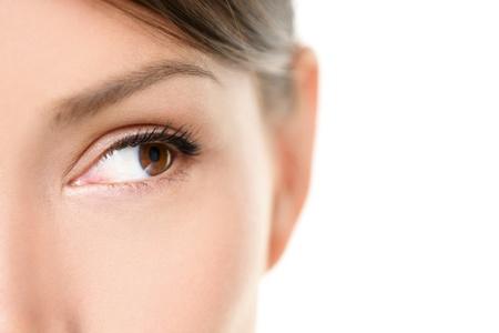 Oog close-up - bruine ogen op zoek naar kant geïsoleerd op een witte achtergrond. Gemengd ras Aziatische blanke vrouw op zoek zijwaarts. Close-up van bruin vrouwelijke oog. Stockfoto