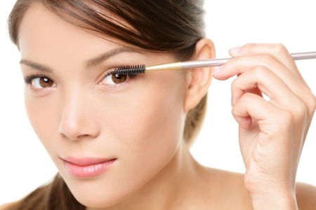 Mascara woman putting makeup on eyes. Asian female model face closeup with eye brush on eyelashes.