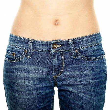 bare body women: Woman waist wearing jeans. Weight loss stomach closeup. Skinny jeans on a healthy slim fit body.
