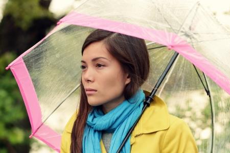 sotto la pioggia: Melancholia - donna malinconica in pioggia sotto l'ombrello che sembra triste infelice e intelligentemente. Ragazza graziosa che cammina sotto un ombrello trasparente piovosa giornata d'autunno caduta. Multirazziale femminile nel suo 20s.