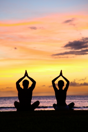 yoga sunset: Yoga meditation - silhouettes of people at sunset. Silhouette of a couple practicing yoga at sunset sitting on a beach in the lotus position with their hands raised against colorful sky. Man and woman Stock Photo