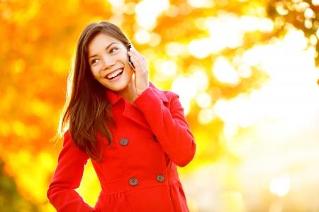 hablando por telefono: Tel�fono inteligente mujer oto�o hablando por tel�fono m�vil en el oto�o. Muchacha del oto�o que tiene una conversaci�n inteligente en sol llamarada del follaje. Retrato de raza mixta Asi�tico Cauc�sico mujer joven en el bosque en los colores del oto�o. Foto de archivo