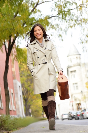 coats: Young stylish female professional holding handbag wearing modern trench coat walking in urban city smiling happy. Multiracial Asian Caucasian female model in her 20s. Stock Photo