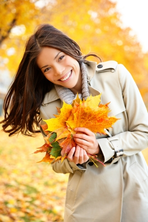 Fall  Autumn woman holding colorful leaves in city park smiling happy. Stylish modern portrait of girl showing colorful leaves outdoor in fall forest foliage. Mixed race Asian Caucasian female model. photo