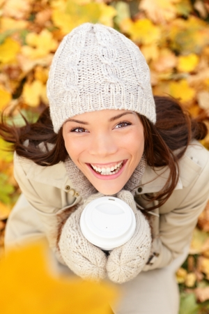 Autumn woman drinking coffee in fall forest. Girl sitting relaxing enjoying hot drink, coffee or tea, from disposable cup. Beautiful female outdoor in autumn colors. Multiracial Asian Caucasian, 20s. photo