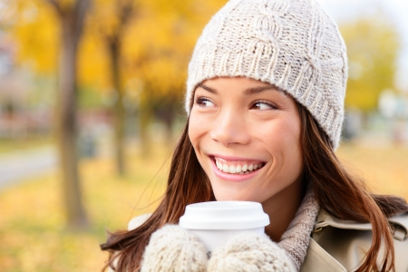 asian woman face: Autumn  fall woman drinking coffee looking at forest foliage copy space thinking. Happy smiling multi-ethnic Asian Chinese  Caucasian female model in red coat enjoying hot drink outdoor.
